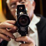 Senior man holding old fashioned Movie Camera.